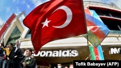 People wave the Turkish (center) national flag and the Azerbaijani flag as they celebrate victory in the streets of Baku on November 10.
