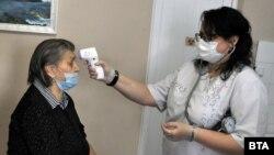 Медицински работник мери температурата на жена в дом за възрастни хора в Бургас