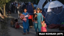Internally displaced Afghans who fled from Kunduz, Takhar, and Baghlan provinces due to battles between the Taliban and Afghan security forces walk past temporary tents at the Sara-e Shamali camp in Kabul on August 11.