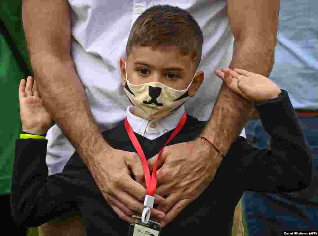 A father with his son wearing a protective face mask wait in front of a school in Bucharest on September 14, where classes started again after the summer break. (AFP/Daniel Mihailescu)
