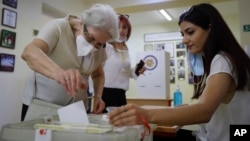 An Armenian woman casts her ballot paper at a polling station in Yerevan on June 20.