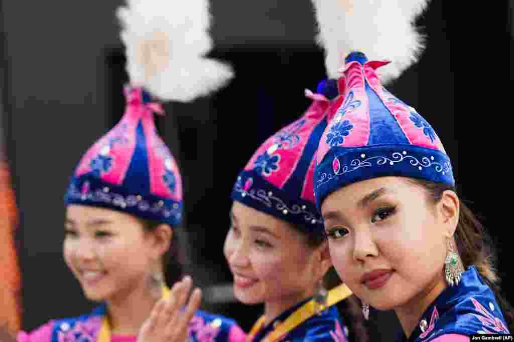 Femei kazace îmbrăcate în haine tradiționale pozează înpavilionul Kazahstanului, la Expo 2020, în Dubai.