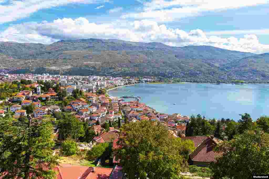 Изглед към Охрид в Северна Македония. Някои местни жители посочват безбройните незаконни постройки, включително хотели, които са одобрени и оставени на място. В същото време по-малки постройки са набелязани за разрушаване. През 2020 г. бяха разкрити документи, показващи как собствениците на 416 незаконно построени имота на брега от македонската страна на Охридското езеро са кандидатствали за узаконяване на строежите им по силата на нов закон.