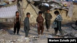 Дети временно перемещенных лиц на фоне мест их проживания в Кабуле. Январь 2021 года.
