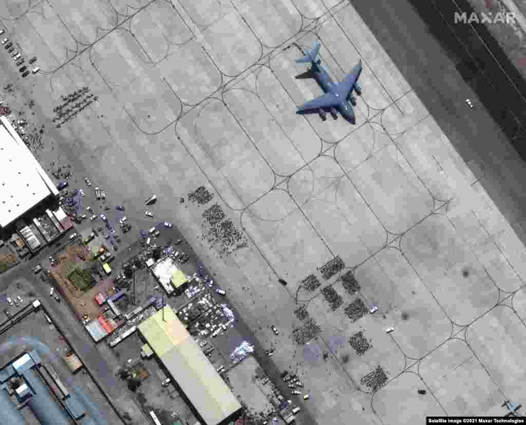 O mulțime de oameni așteaptă să fie evacuați pe pista aeroportului Internațional Hamid Karzai din Kabul. Un avion de transport C-17 este gata de decolare, pe 23 august.