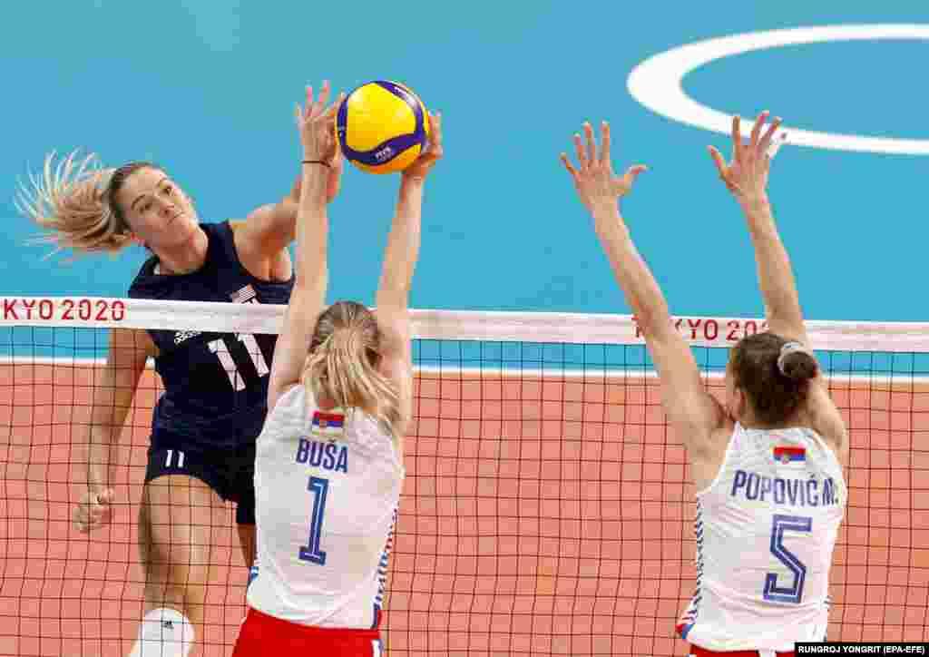 Андреа Дрюс (слева) из США в бою против Бьянки Буса (слева) и Мины Поповице (справа) из Сербии во время полуфинального матча по волейболу между США и Сербией на Олимпийских играх 2020 года в Токио на Ариаке Арена