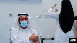 Медицина қызметкері тұрғынға коронавирусқа қарсы вакцина салып жатыр.