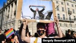 Протестиращ в Будапеща държи снимка, изобразяваща Виктор Орбан, който вдига шал с цветовете на дъгата