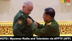 Russia's Deputy Defense Minister Aleksandr Fomin (left) receives a medal from Burma's armed forces chief, Senior General Min Aung Hlaing, on March 26.
