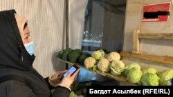 Көкөніс сатып алуға ақша аудару үшін саудагердің қабырғаға жазып қойған телефон нөмірін теріп тұрған тұтынушы. Алматы, 25 ақпан 2021 жыл.