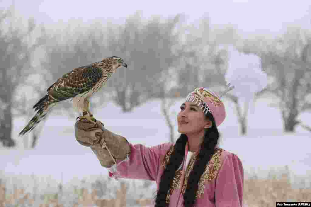 Млада жена в казахстанска народна носия държи ловен сокол по време на състезанието.