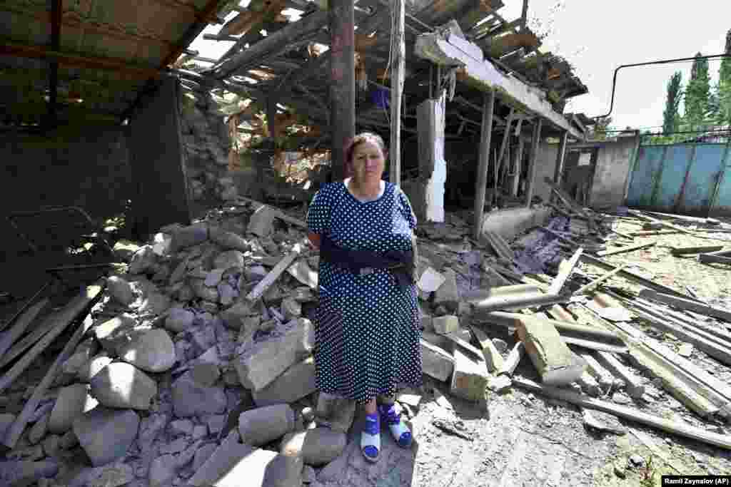 A woman stands in front of her damaged home in Azerbaijan's northern Tovuz region on July 16 after cross-border fighting resumed between Armenian and Azerbaijani forces.