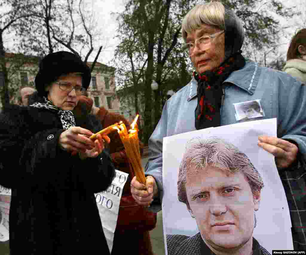 Women hold a poster of Litvinenko and light candles during a Moscow memorial on November 22, 2008.