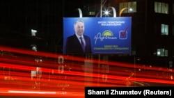 Автомобили проезжают мимо предвыборного плаката партии «Нур Отан» в Алматы. 11 марта 2016 года.