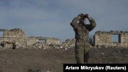 Этнический армянин смотрит в бинокль на боевых позициях возле села Тагавард в районе Нагорного Карабаха, 11 января 2021 года.