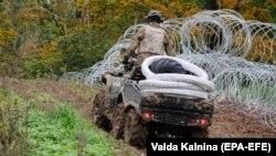 Солдат Збройних сил Латвії патрулює кордон із Білоруссю, нещодавно посилений колючим дротом, 28 вересня 2021 року
