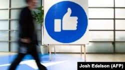 """A Facebook alkalmazottja a """"like"""" jelzés mellett sétál a Facebook központjában, Kaliforniában, 2019. október 23-án"""