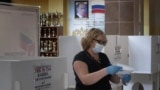 RUSSIA -- A woman wearing a face mask and gloves prepares to cast her ballot during early voting in a referendum on amendments to the Russian Constitution next to a portrait of Russian President Vladimir Putin at a polling station in Moscow, June 25, 2020