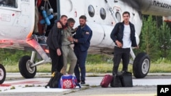 Anatoly Prytkov, one of the pilots of the An-28, is helped by his colleagues to exit a helicopter that was also carrying the other surviving passengers at an airport outside Tomsk.