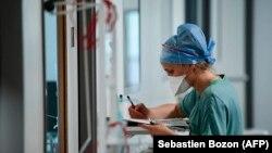 Egy egészségügyi dolgozó a Covid-betegek nyilvántartását végzi a Pasteur kórház intenzív osztályán Franciaország keleti részén, Colmarban. 2021. április 22.