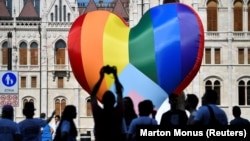 People gather in front of a huge rainbow balloon put up by members of Amnesty International and Hatter, an NGO promoting LGBT rights, outside Hungary's parliament in Budapest on July 8.