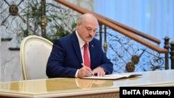Александр Лукашенко подписывает документ после присяги