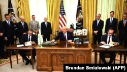U.S. President Donald Trump (center) speaks before Kosovar Prime Minister Avdullah Hoti (right) and Serbian President Aleksandar Vucic sign an agreement on opening economic relations, in the Oval Office at the White House on September 4.