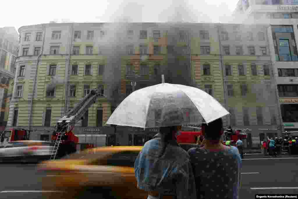 People watch as firefighters work to extinguish a blaze at a building in central Moscow. (Reuters/Evgenia Novozhenina)