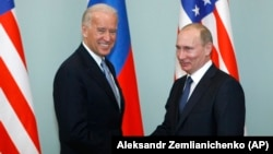Then-U.S. Vice President Joe Biden (left) shakes hands with Putin, who was then Russian prime minister, in Moscow on March 10, 2011.