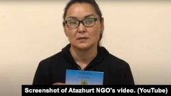 Этническая казашка из Синьцзяна Кайша Акан, незаконно пересекшая границу Казахстана, держит в руках удостоверение лица, ищущего убежище. Скриншот с видео на канале «Атажурт».