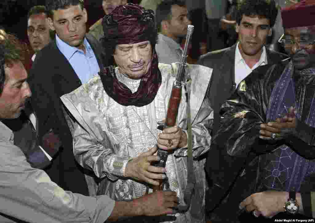 Бывший лидер Ливии Муаммар Каддафи с винтовкой, подаренной ему вождями племен в октябре 2009 года.