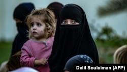 Сириядағы босқындар лагерьлерінде тұрып жатқан баласын көтеріп тұрған әйел.