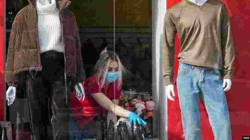 Вітрина магазину одягу в Сімферополі. Продавчиня працює у захисній масці