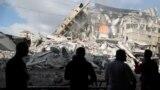 Палестинцы смотрят на разрушенное в результате воздушного удара израильских ВВС здание в секторе Газа, 13 мая 2021 года.