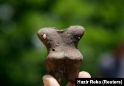Një aerkelog në Kosovë tregon një pjesë të një ene të qeramikës të gjetur më 2011 në fshatin Reshan, në afërsi të Prishtinës. Ky vendbanim besohet se është i vjetër 6.000 vjet.