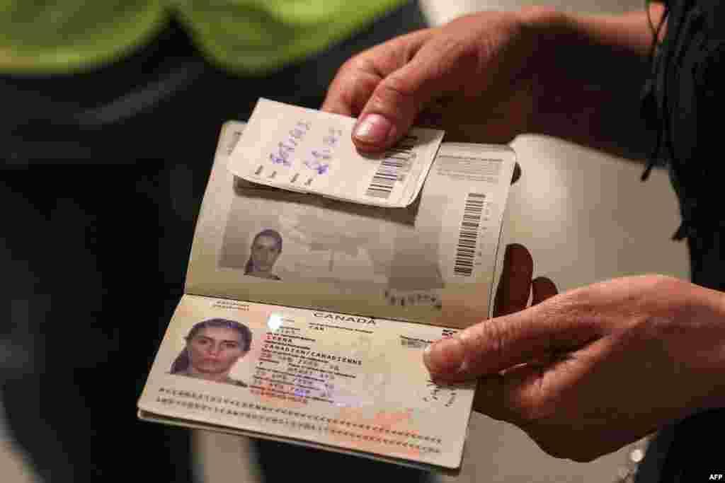 Egy kanadai állampolgár az útlevelét mutatja, miután a járat megérkezett Katarba
