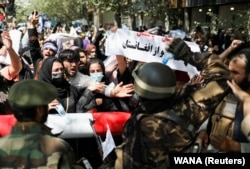 Talibanski borci ispred demonstranata koji traže prava žena i protestuju protiv talibana u Kabulu 7. septembra.