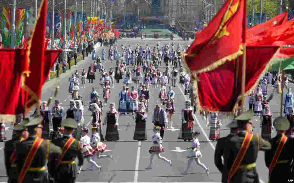 Belarusian youths wearing traditional national costumes take part in a Victory Day parade in Minsk.