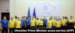 Прем'єр-міністр Денис Шмигаль та члени його уряду позують у футболках національної збірної України з футболу під час засідання Кабінету міністрів. Київ, 30 червня 2021року