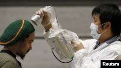 A man is tested for possible radiation exposure at an evacuation center in Kuriayama