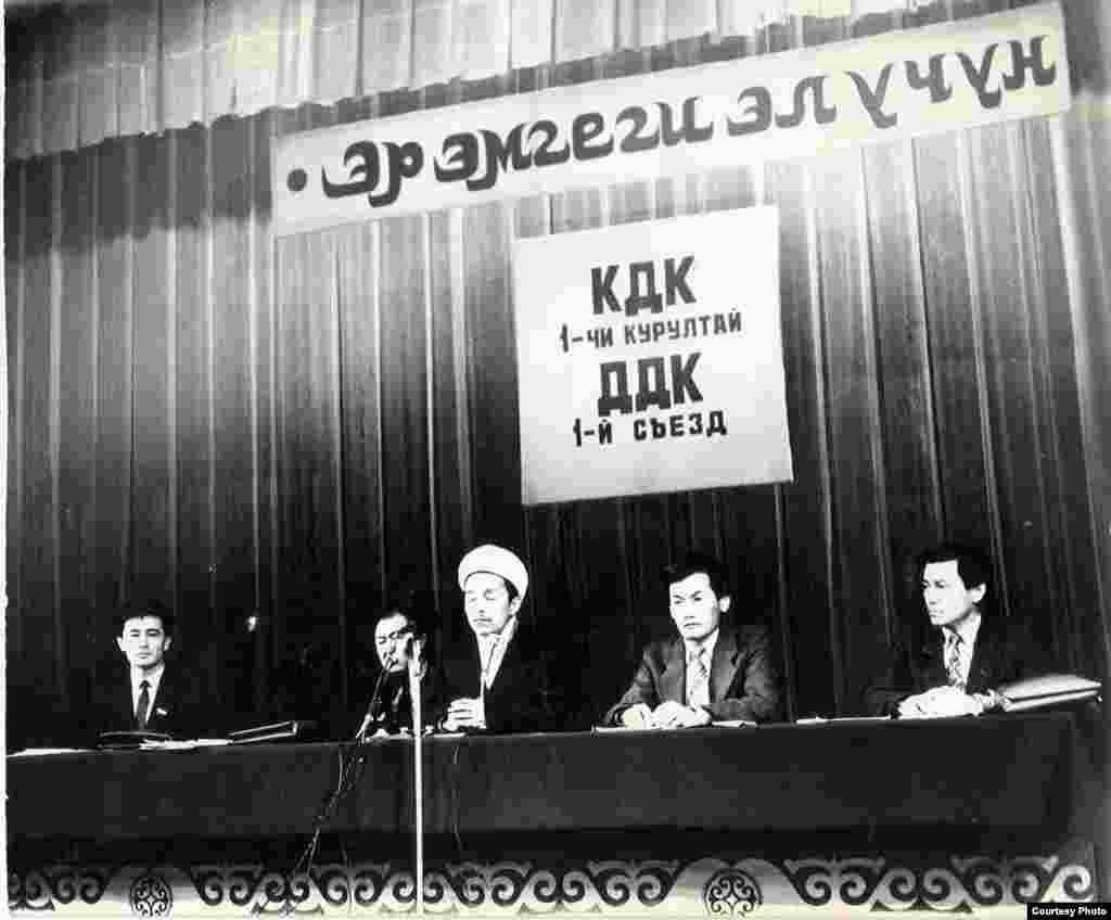 1991-жылдын 9-10-февралында өткөрүлгөн КДКнын Биринчи курултайынын ачылыш салтанаты маалында. Төрдө отургандар - Өмүрбек Текебаев, депутат жана КДКнын мүчөсү, Казат Акматов, депутат жана КДКнын теңтөрагасы, Дүйшөнбек Отонбай уулу, Кыргызстандын муфтийинин катчысы, Кадыр Маматказиев, КДКнын теңтөрагасы жана Жыпар Жекшеев, КДКнын теңтөрагасы (солдон оңго).