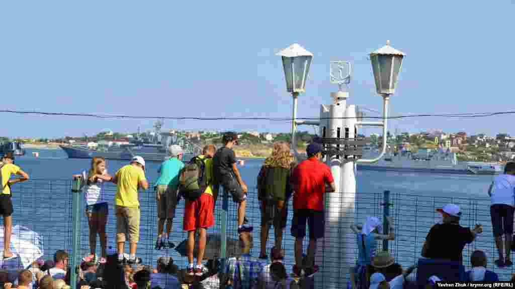 Дети взбирались на ограждения, чтобы увидеть происходящее в Севастопольской бухте