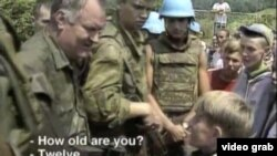 A screen grab of Bosnian Serb General Ratko Mladic meeting a Bosnian Muslim boy shortly before the 1995 massacre in Srebrenica.