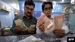 FILE: Money dealers counts Pakistani rupees (R) and US dollars at a currency exchange in Islamabad.