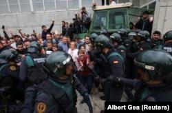 Испанская полиция штурмует один из избирательных участков в Барселоне. 1 октября