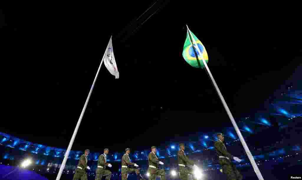 Brazilian soldiers march past the Olympic and Braziilian flags.