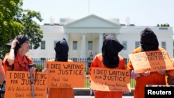 Activists wearing orange jumpsuits mark the 100th day of a prisoners' hunger strike at Guantanamo Bay during a protest in May in front of the White House in Washington, D.C.