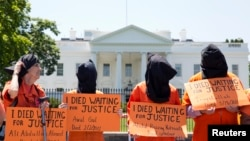 Активисты в оранжевых комбинезонах перед Белым домом во время акции протеста, посвященной голодовке заключенных Гуантанамо, 17 мая 2013 года.