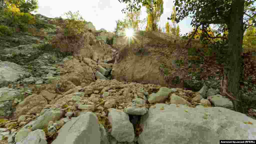 Крутой южный берег озера весь в камнях, фрагментах блоков