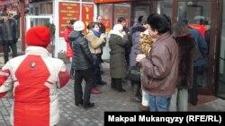 Вкладчики, напуганные слухами о банкротстве банков, стоят в очереди в банк, чтобы снять деньги с депозитов. Алматы, 20 февраля 2014 года.